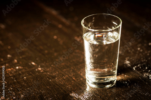 Tuinposter Alcohol Alcoholism concept - a glass of alcohol on old boards