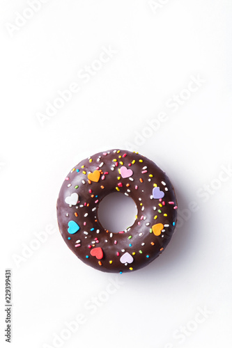 Chocolate donut with sprinkles on top isolated on a white background viewed from above. Top view. Copy space.