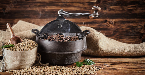 Old vintage cast iron coffee roaster and raw beans - 229402240