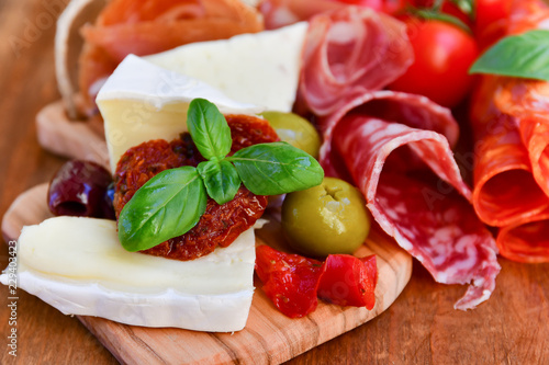 Keuken foto achterwand Assortiment Traditional italian antipasto with prosciutto, parmesan cheese and brie cheese, sun-dried tomatoes, salami, green olives and Basil, wooden table, Italian restaurant, selective focus