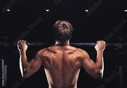 Fotografie, Obraz  Rear view of muscular man doing pull up exercise on horizontal bar