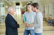 professor talking to students in school corridor