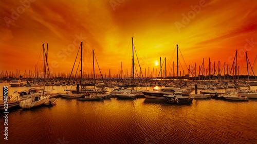 Obraz na płótnie Żeglowanie łodzie przy schronieniem przeciw pomarańczowemu zmierzchowi