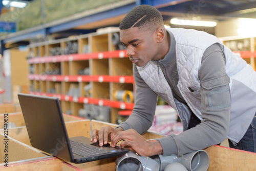 фотография  young manual worker using a laptop in a warehouse