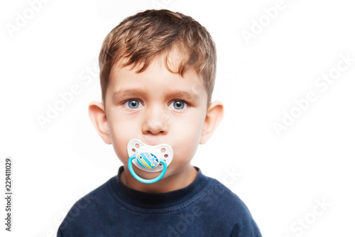 Fotomural Little boy with a serious face and with pacifier in his mouth on a white backgro