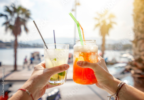 Cocktails with straws in a glass in human hands on background of the city, leisure and travel, entertainment, bars and restaurants, refreshments