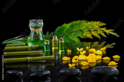 Keuken foto achterwand Spa Beautiful spa composition with zen basalt stones and bamboo essential oil plants and flowers on black background