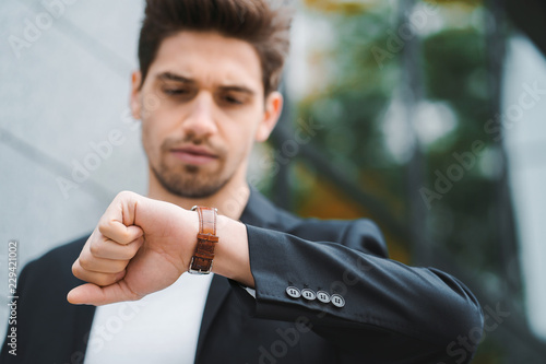 Handsome Businessman Or Student Looks At Watch Young Man In