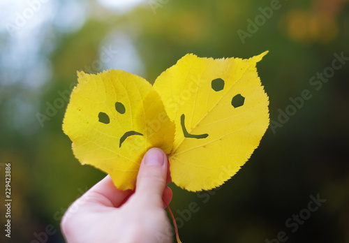 Autumn leaves sad and happy face in a hand
