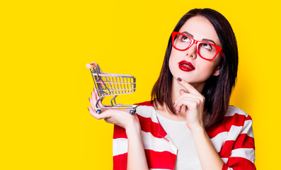 Fototapeta Portrait of a young woman in glasses with shopping cart on yellow background