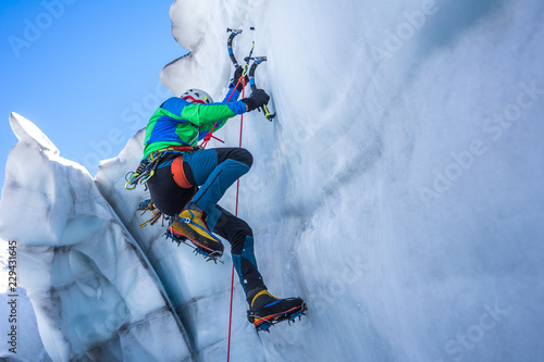 Obraz na plátně Epic shot of an ice climber climbing on a wall of ice