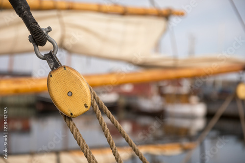 Staande foto Schip Pulley for sails and ropes made from wood on an old sail boat, with sail and other boats out of focus in the background.