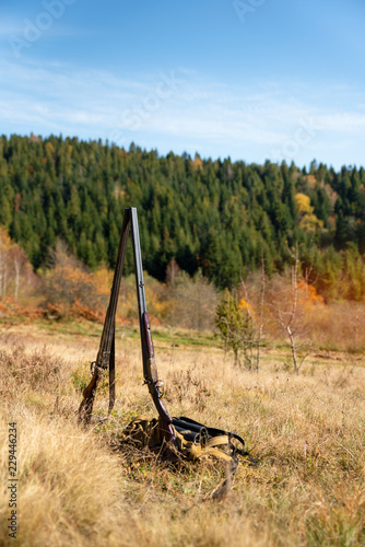 Two hunting double-barreled shotgun stand side by side in the middle of nature, retro rifle. Natural landscape. Concept of hunting, outdoor sports, hobbies and lifestyle