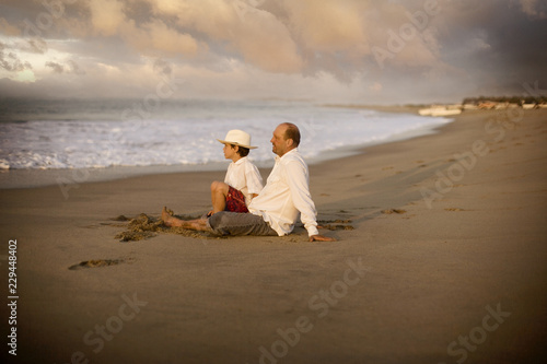 Tuinposter Strand Side view of a father and his son sitting by the beach.