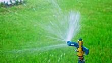 Slow-motion Of Garden Sprinkler Spreading Water All Over The Turf