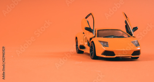 Photo  Toy orange car, on orange background. Sports car, close-up shot