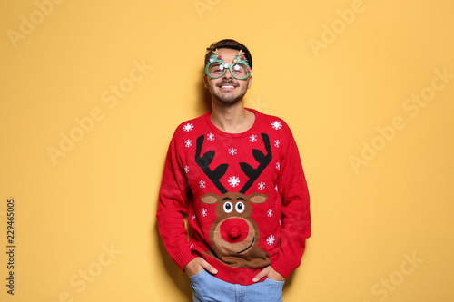 Fotografia  Young man in Christmas sweater with party glasses on color background