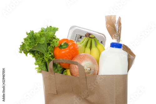 Fotografía  Brown eco friendly grocery bag with bottle of milk, carton of eggs, bag of bread, bananas, lettuce, bell pepper and onion, isolated on white