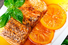 Honey Glazed Fillet Salmon With Orange Slices, Spices And Basil On White Plate On Dark Background. Delicious Dish Of Seafood.