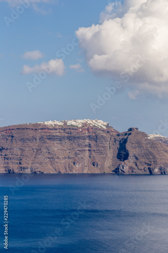 Photo Stands Melon Oia Santorini Island. View of Oia village with white houses on red rocks caldera