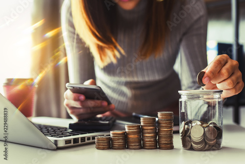 Fotomural businesswoman holding coins putting in glass with using smartphone and calculato
