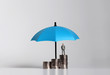 canvas print picture - Miniature businessman standing on a pile of coins with umbrella.