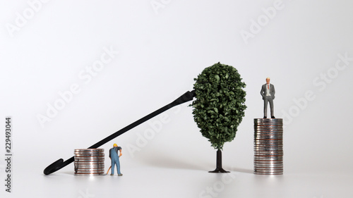 Fotografia, Obraz  Miniature people with pile of coins and miniature trees