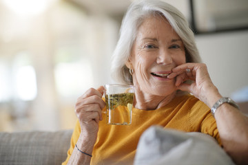 Fototapeta Beautiful senior woman at home with cup of loose leaf tea