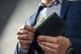 Elegancki mężczyzna w garniturze wyciąga pieniądze z portfela. Koncepcja zarządzania pieniędzmi.