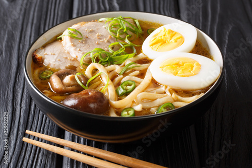 Freshly cooked soup with udon noodles, pork, boiled eggs, mushrooms and green onions close-up on a black table. horizontal