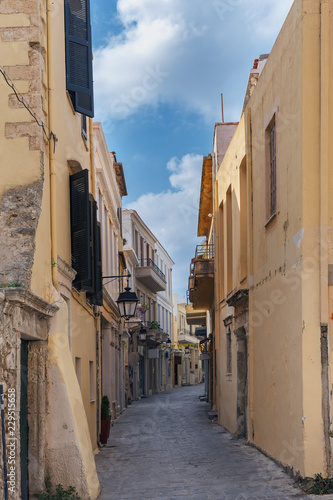Narrow street in the old part of the Greek city with characteristic southern architecture