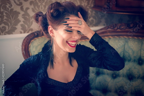 Photo Sexy Caucasian model looking like a vampire laughing on a couch, having sculpting make-up and cocktail dress with big cleveage