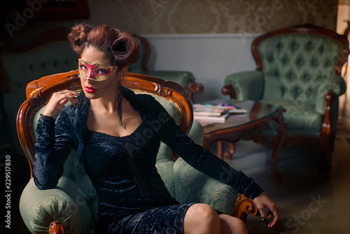 Sexy Caucasian model with carnival red mask standing on a couch, with her black stiletto nails, sculpting make-up and cocktail dress with big cleveage Fototapet