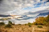 Fototapeta Tęcza - Dramatic cloudy italian valley with mountains
