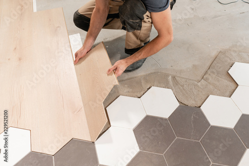 Male Worker Installing New Wooden Laminate Flooring The Combination Of Wood Panels Of Laminate And Ceramic Tiles In The Form Of Honeycomb Kitchen Renovation Buy This Stock Photo And Explore Similar