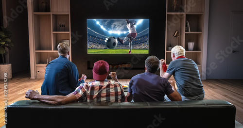Group of fans are watching a soccer moment on the TV and celebrating a goal, sitting on the couch in the living room Canvas