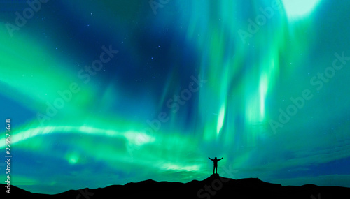 Poster Noorderlicht Aurora borealis with silhouette standing man on the mountain.Freedom traveller journey concept