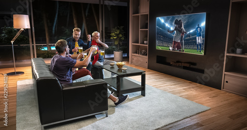 Fotografía  Group of fans are watching a soccer moment on the TV and celebrating a goal, sitting on the couch in the living room