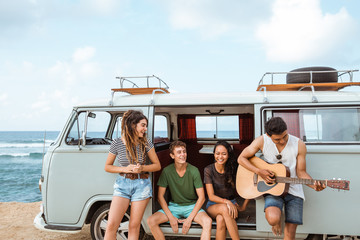 Hipster friends in retro van at the beach
