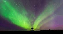 Aurora Borealis With Silhouette Love Romantic Couple On The Mountain.Honeymoon Travel Concept
