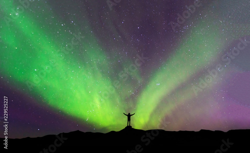 Poster Aurore polaire Aurora borealis with silhouette standing man on the mountain.Freedom traveller journey concept