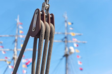 Close Up Of A Modern Pulley With Ropes Against A Blue Sky And Masts With Colored Flags And Selective Focus