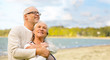 canvas print picture - old age, retirement and people concept - happy senior couple hugging over beach background