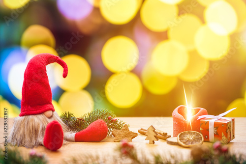 Fotografie, Obraz  Christmas dwarf with bokeh lights in background and fir branch with ignited adve