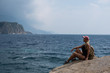 A young girl with blond hair sits on top of a mountain and looks at the sea and beach Relax and travel on nature.