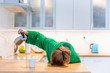 canvas print picture - Tired woman sleeping on the table in the kitchen at breakfast. Trying to drink morning coffee