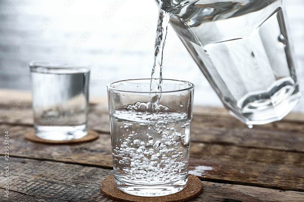 Fototapety, obrazy: Pouring of fresh water from jug into glass on wooden table