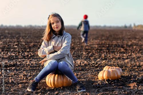 Valokuvatapetti Cute little girl sitting on pumpkin in autumn field