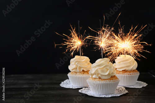 Photo  Delicious cupcakes with sparklers on wooden table against dark background