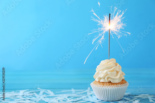 Delicious cupcake with sparkler on color background Wallpaper Mural